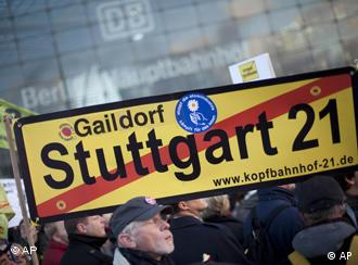 Demonstrators hold a banner with the words Stuttgart 21 crossed through in red