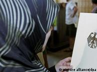 Eine Frau mit Kopftuch schaut sich die Einbürgerungsurkunde der Bundesrepublik Deutschland an (Foto: dpa)