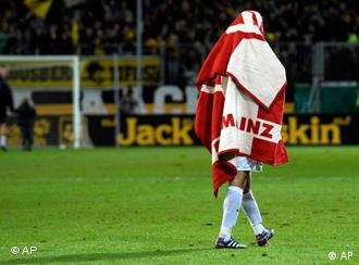 Mainz player walks off pitch covered in team flag
