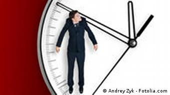 Businessman hangs on an arrow of clock, isolated on red background. Fotolia_10981793_Subscription_L.jpg