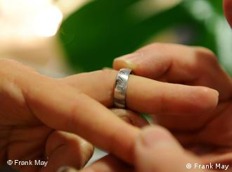A wedding ring is slipped on to a finger
