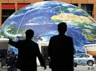 Two delegates to the World Summit on Sustainable Development walk in front of a giant globe in Sandton Square, adjacent to the Sandton Convention Centre in Johannesburg, South Africa, Monday Aug. 26, 2002. (AP Photo/Jon Hrusa)