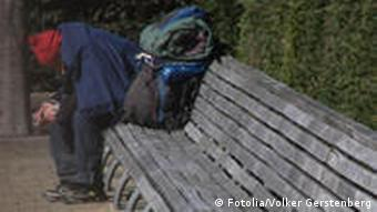 A homeless person on a park bench