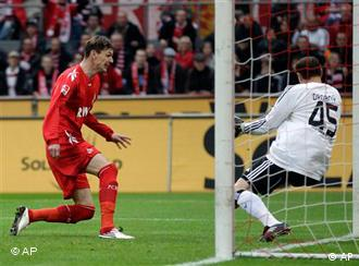 Cologne's Milivoje Novakovic of Slovenia, left, scores against Hamburg's goalkeeper Jaroslav Drobny