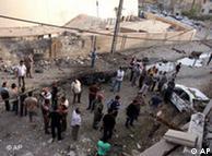 چند شهروند  عراقی به آثار انفجار بمب در برابر کلیسا مینگرند