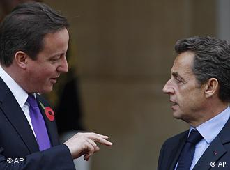 French President Nicolas Sarkozy, right, talks to British Prime Minister David Cameron