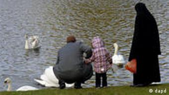 A young family, including a women wearing a burka feed ducks