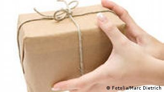 Female hands holding a brown parcel. (Photo: Fotolia)