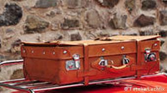 Symbolbild Koffer Auto Dach Urlaub Reise