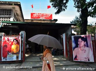 A Myanmar Buddhist nun walks in front of the NLD party headquarters in Yangon