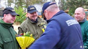 a man hands over a bunch of flowers to the bomb experts