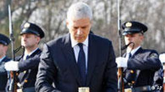 Serbian President Boris Tadic holds a candle as he pays respect at a pig farm Ovcara where more than 200 Croats dragged out of a local hospital were slain by Serbs when they seized Vukovar, eastern Croatia, Thursday, Nov. 4, 2010. Tadic became his country's first leader to come to Vukovar since the 1991 war, when Serbs' relentless bombardment leveled the town to the ground, leaving scores of Croats dead and forcing others out. (AP Photo/Darko Bandic)