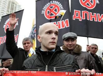 Russian nationalists dressed in black carry banners