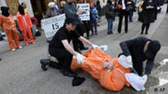 Mike Morice, center, and other members of World Can't Wait group perform a live waterboarding demonstration outside the Spanish Consulate in Manhattan to urge prosecution in Spain of the alleged involvement of Bush administration officials in the torture of terror suspects, Thursday, April 23, 2009 in New York.