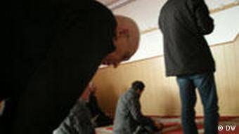 Man bowing down in a mosque's praying room
