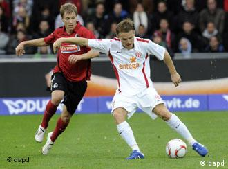 Mainz player Eugen Polanski, right, and Freiburg's Anton Putsila challenge for the ball