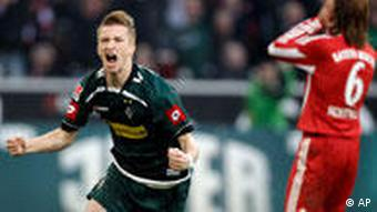 Moenchengladbach's Marco Reus, left, celebrates after scoring while Bayern's Martin Demichelis of Argentina reacts during the German first division Bundesliga soccer match between VfL Borussia Moenchengladbach and Bayern Munich in Moenchengladbach, Germany, Saturday, Nov. 6, 2010.