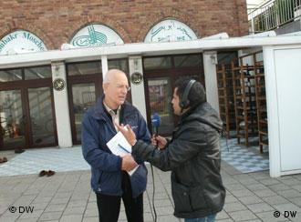 Reporter holding up a microphone to interview partner infront of a mosque
