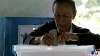 Old woman casts ballot in Burma