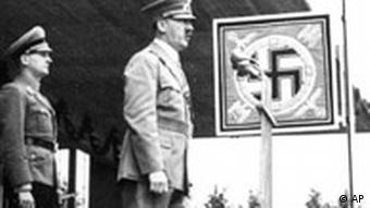 Hitler hält eine Rede mit Hakenkreuz im Hintergrund