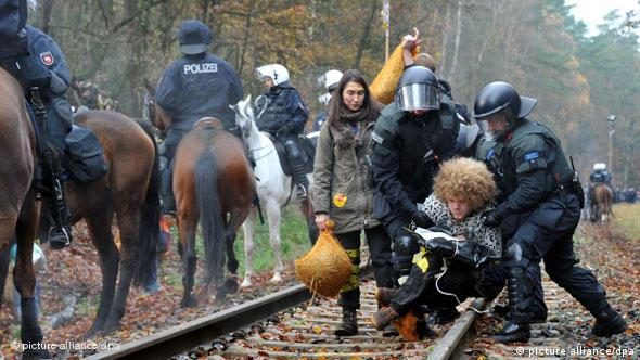 An activist is forcibly taken off the tracks by police