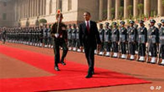 Obama walking on red carpet in front of troops