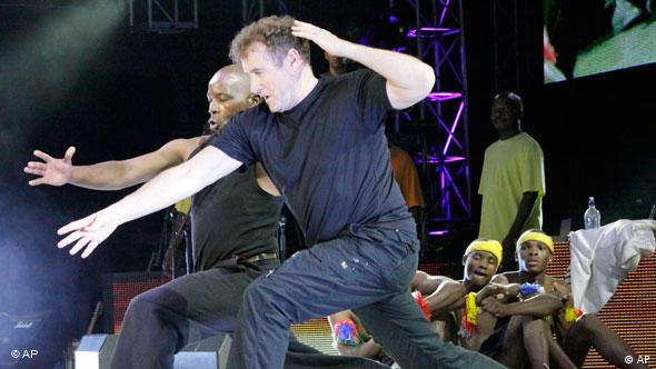 Johnny Clegg, known as the White Zulu, performs a dance routine during a concert in Johannesburg Copyright: AP Photo/Denis Farrell