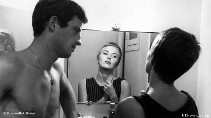 Filmszene: Jean-Paul Belmondo schaut Jean Seberg an, die sich im Spiegel betrachtet.