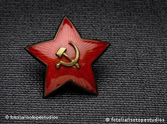 A hammer and sickle on a red star pin