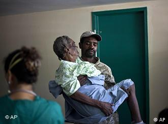A woman suffering from cholera symptoms is carried by a volunteer at the hospital in Archaie, Haiti, Nov. 8, 2010