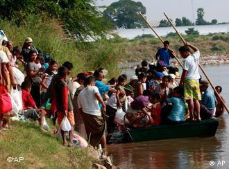 Myanmar refugees board a boat as they return home from Thailand Tuesday