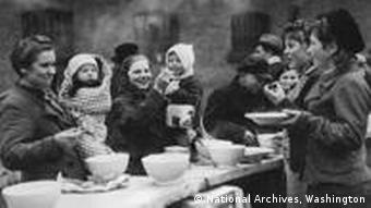 Woman and children eating after liberation