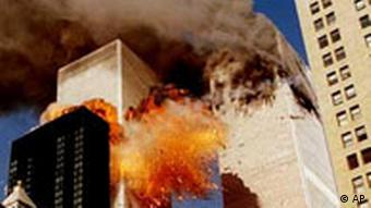 Smoke billows from one of the towers of the World Trade Center as flames and debris explode from the second tower