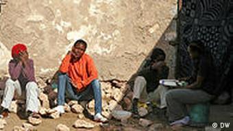 Abgemagerte junge Männer sitzen vor einer Steinmauer (Foto: DW)