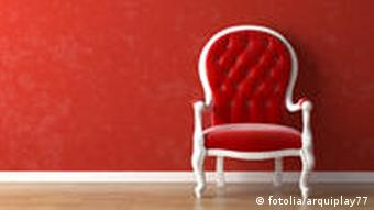 An empty chair in front of a red wall