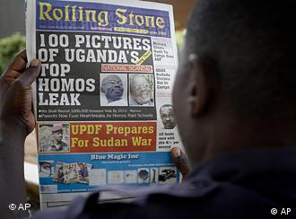 A Ugandan man reads the headline of the Ugandan newspaper Rolling Stone. 100 Pictures of Uganda's Top Homos Leak _ Hang Them.