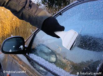 A man scraping ice from car window