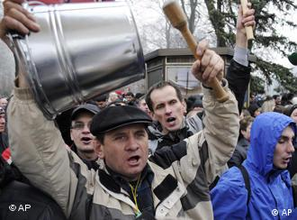 Protesters bang metal buckets and shout slogans protesting the draft tax law