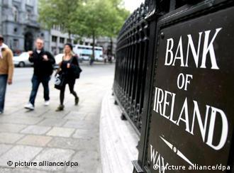 Pedestrians walks past a name plaque for the Bank of Ireland