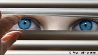 Blue eyes looking through blinds