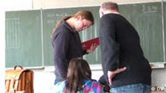 The special education teacher and the history teacher help a student in Marcel's class