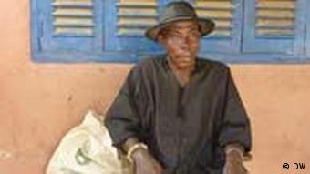 Ein alter Mann sitzt vor seinem Haus (Foto: von Hein/DW)