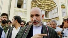 Afghan President Hamid Karzai speaks to a group in front of a Mosque in Kandahar prior to an assassination attempt Thursday Sept. 5, 2002 in Kandahar. Karzai was in Kandahar for his brother's wedding celebrations.(AP Photo/Ed Wray)