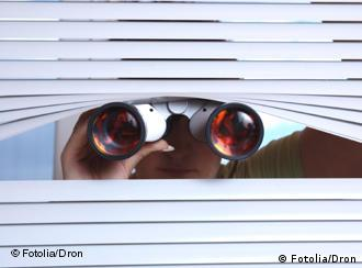 A pair of binoculars peek out from an otherwise closed set of blinds at a window