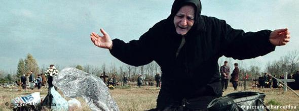 An elderly woman cries over a grave in the cemetary in Vukovar during the war