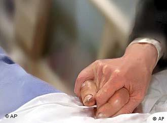 Hands clasped with person in hospital bed, partial graphic