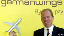 Chairman of the new created low budget airline Germanwings, Friedrich-Wilhelm Weitholz is pictured in front of a company logo as an unidentified person moves a Germanwings plane at the airport in Cologne, Friday Sept.6, 2002. (AP Photo/Frank Augstein)