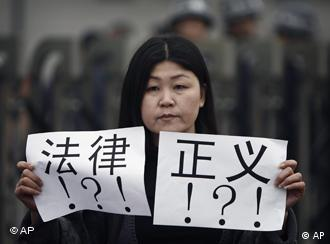 An activist holds papers bearing the words law and justice outside a court house during the trial of Zhao Lianhai in Beijing, Tuesday, March 30, 2010. Zhao Lianhai, who organized a support group for parents of children sickened in one of China's worst food safety scandals pleaded not guilty Tuesday to charges of inciting social disorder, his lawyer said. (AP Photo/Andy Wong)