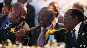 Zimbabwean Prime Minster Morgan Tsvangirai, center, chats to Mines and Minerals Minister, Orbert Mpofu, left and Zanu PF Chairman, Simon Khaya Moyo, right, following the granting of a Kimberley Process certificate to Zimbabwe in Harare, Wednesday, Aug. 11, 2010.