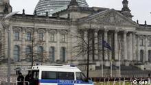 Zwei Polizsten stehen am Montag (22.11.10) in Berlin neben einem Einsatzfahrzeug der Polizei vor dem Reichtagsgebaeude, das von Absperrgittern umgeben ist. Die Kuppel und die Dachterrasse des Reichstagsgebaeudes sind bis auf Weiteres fuer Besucher gesperrt. Dies teilte das Parlament am Montag mit. Die Sicherheitsbehoerden gehen seit Tagen von einer erhoehten Terrorgefahr fuer Deutschland, insbesondere fuer Berlin aus. (zu dapd-Text) Foto: Steffi Loos/dapd